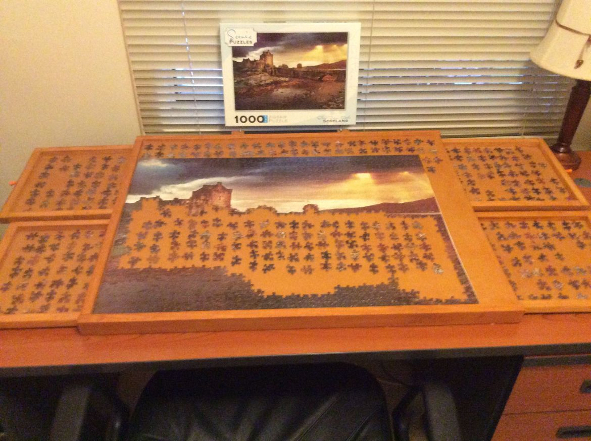 Jigsaw puzzle table with drawers to hold loose pieces of puzzles. Table tilts upwards to ease stretching.