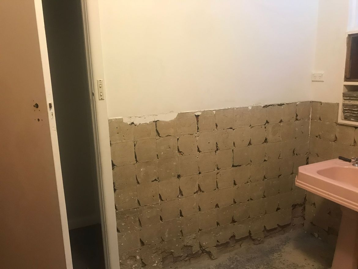 Wall needs to be tiled, but this render is not even and needs to be grounded somewhat. It is more raised than the plaster and thicker at the bottom.