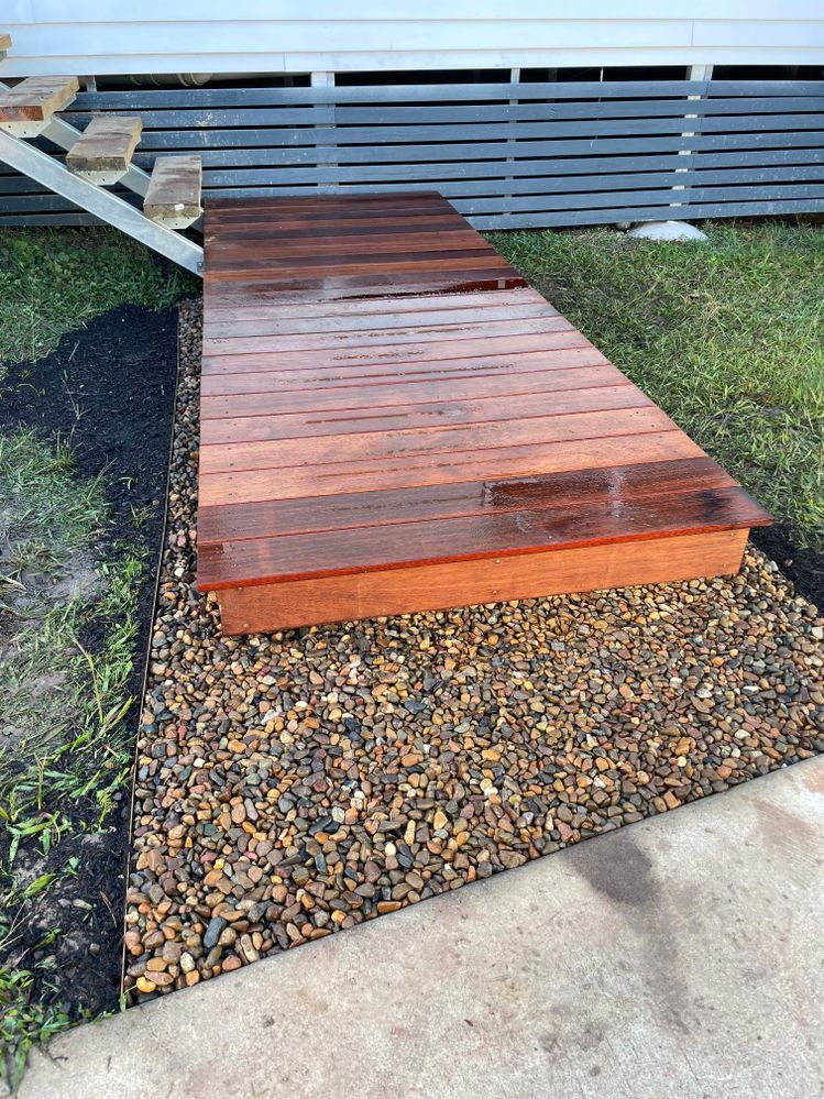 Deck laid. 140mm boards. This is same size as bearers so can also be used to conceal them on exposed faces. Another layer of drainage mat laid onto drainage gravel around edges and then dressed with river pebbles.