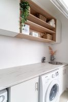 Overhead cabinetry created more storage in this European-style laundry