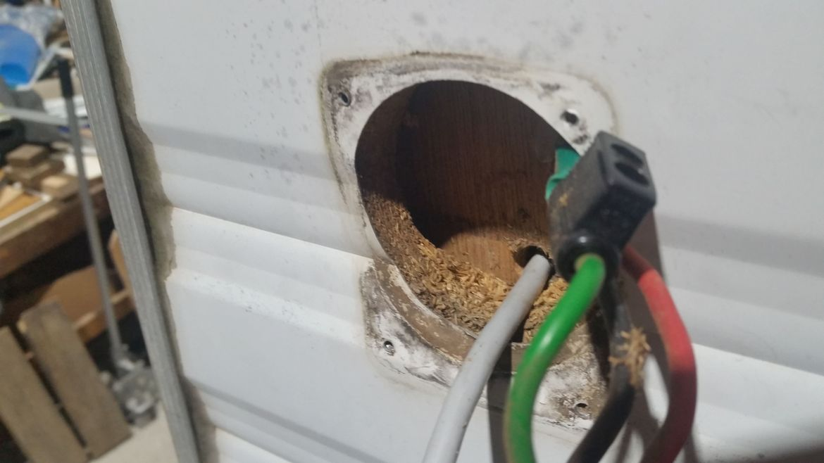 Particle board mounting in wall behind power inlet disintegrating because of water leaks.